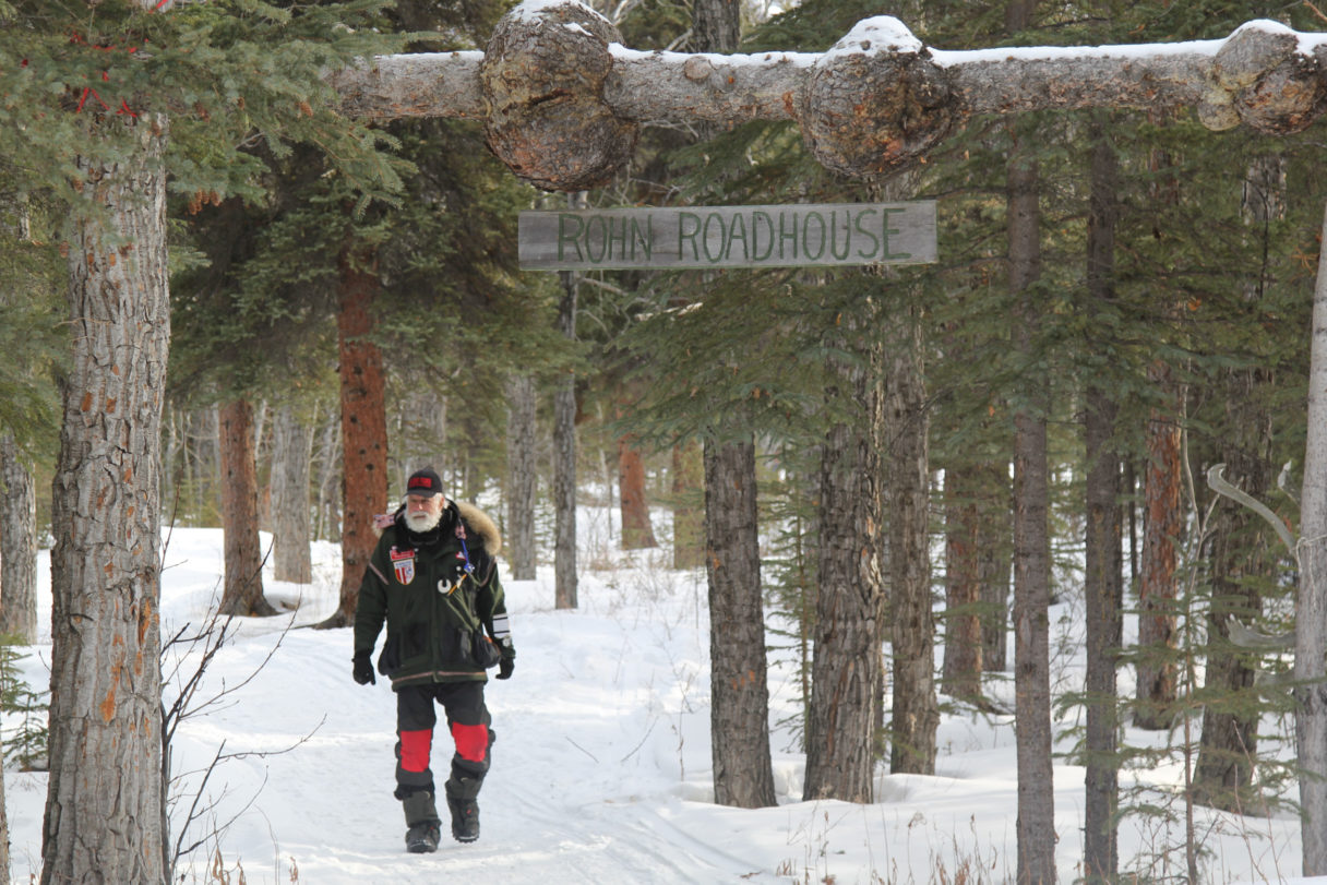 """Man in black parka walks along snowy trail through the woods; over him is a hand-carved wooden sign that reads """"Rohn Roadhouse."""""""