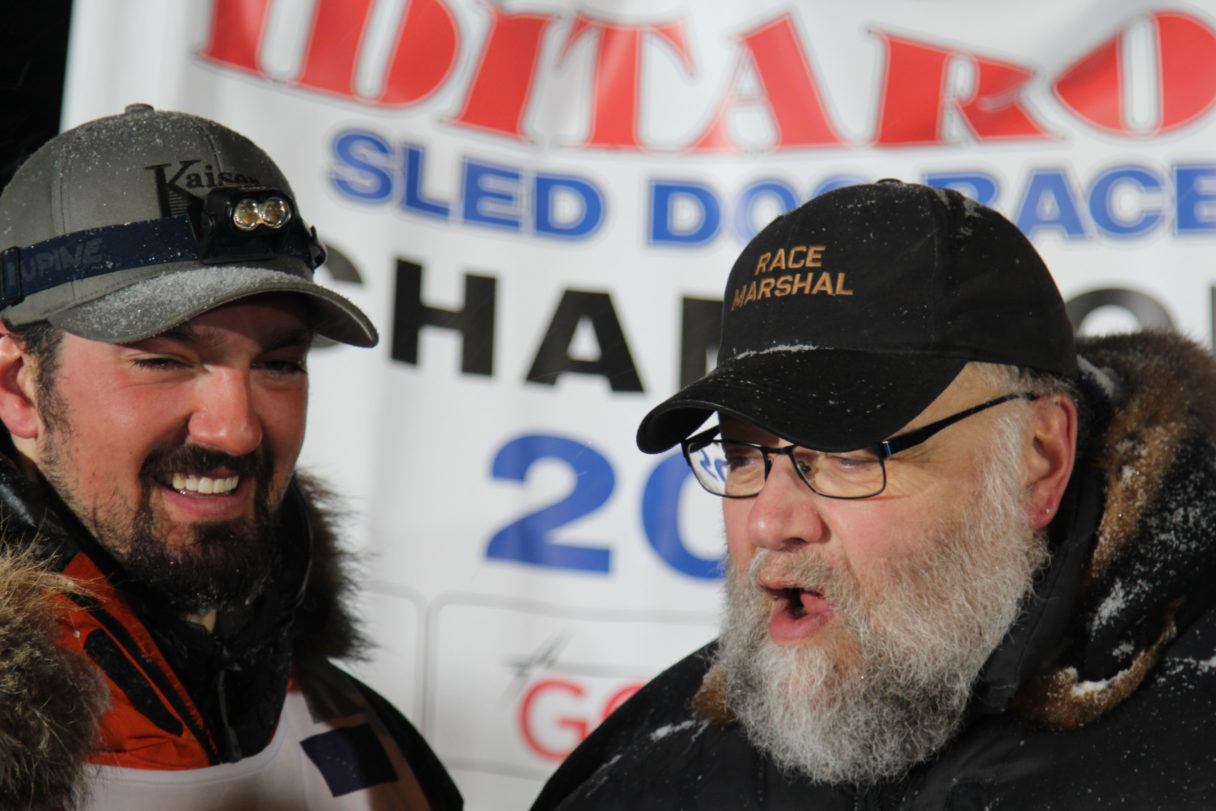 "Two men stand chatting in front of a banner reading ""Iditarod Sled Dog Race Champion."""