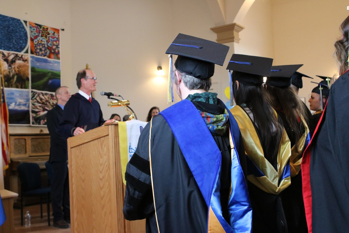 Man at podium stands before crowd of graduates wearing traditional academic robes and mortarboards