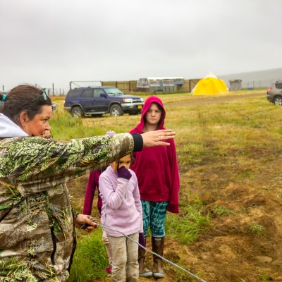 Woman in camouflage jacket stands on grassy tundra next to huddle of children.