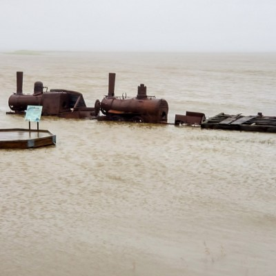 Rusty ruins of old steam locomotive surrounded by water and mist