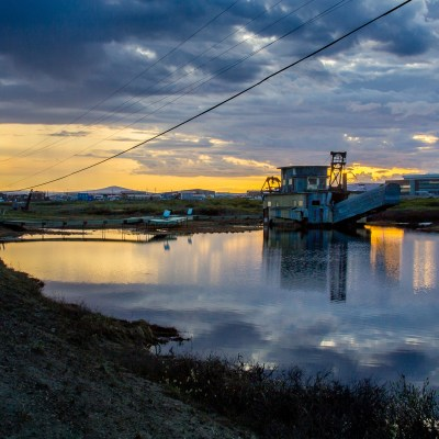 Sunset landscape of gold dredge in small pond in rural Alaska town