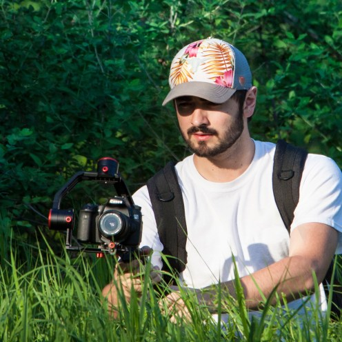 Man standing in vibrantly green, tall grass holds gimbal with digital camera attached