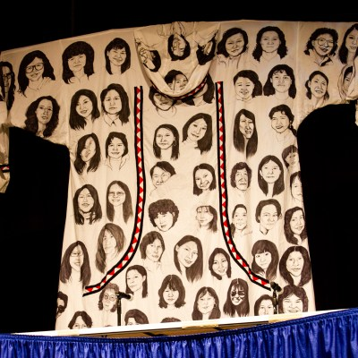 A photo of an art piece, a qaspeq with painted faces of women, hung at 2019 Alaska Federation of Natives.