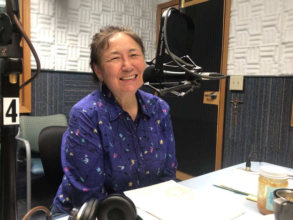 Mary Jane Litchard sitting in front of a microphone.
