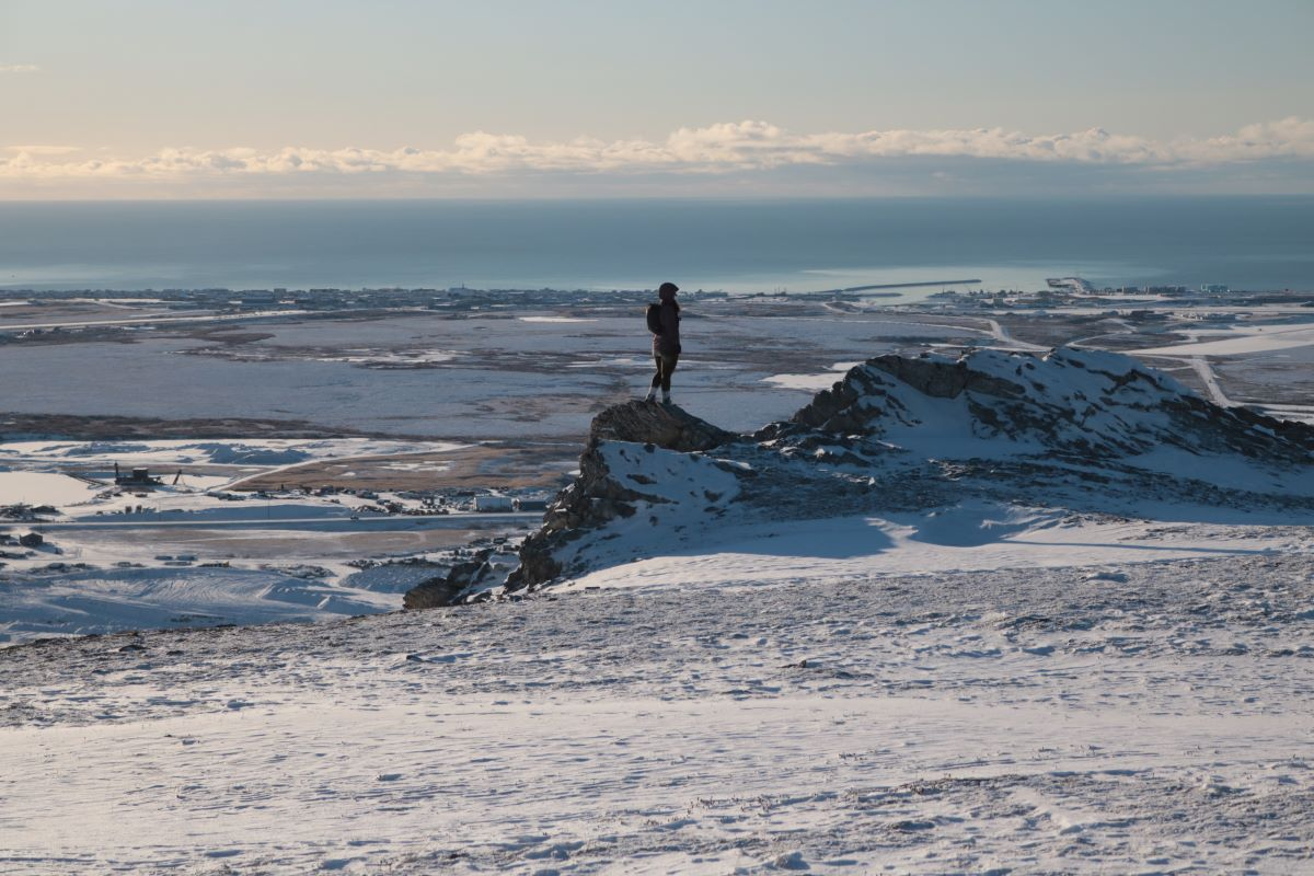 Woman standing on hill overlooking Nome.