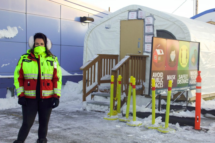 Woman wearing a bright reflective jacket and face covering standing outside COVID tent