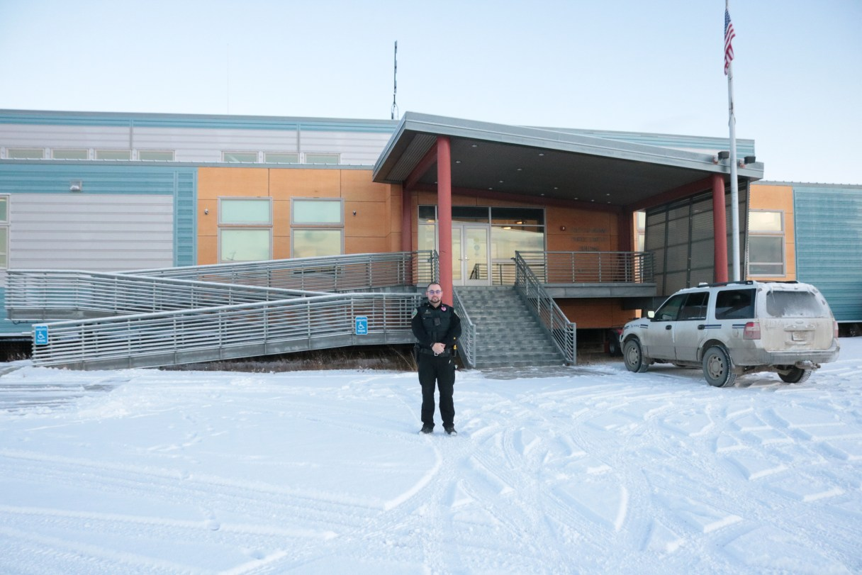 Police officer standing in front of Nome Police Dept. in the winter.