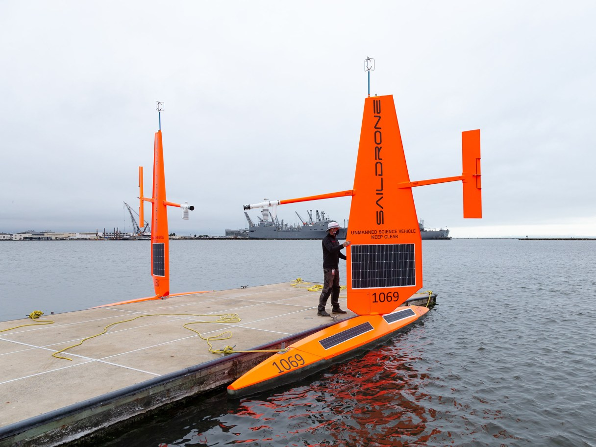 a dock with a man inspecting a saildrone.