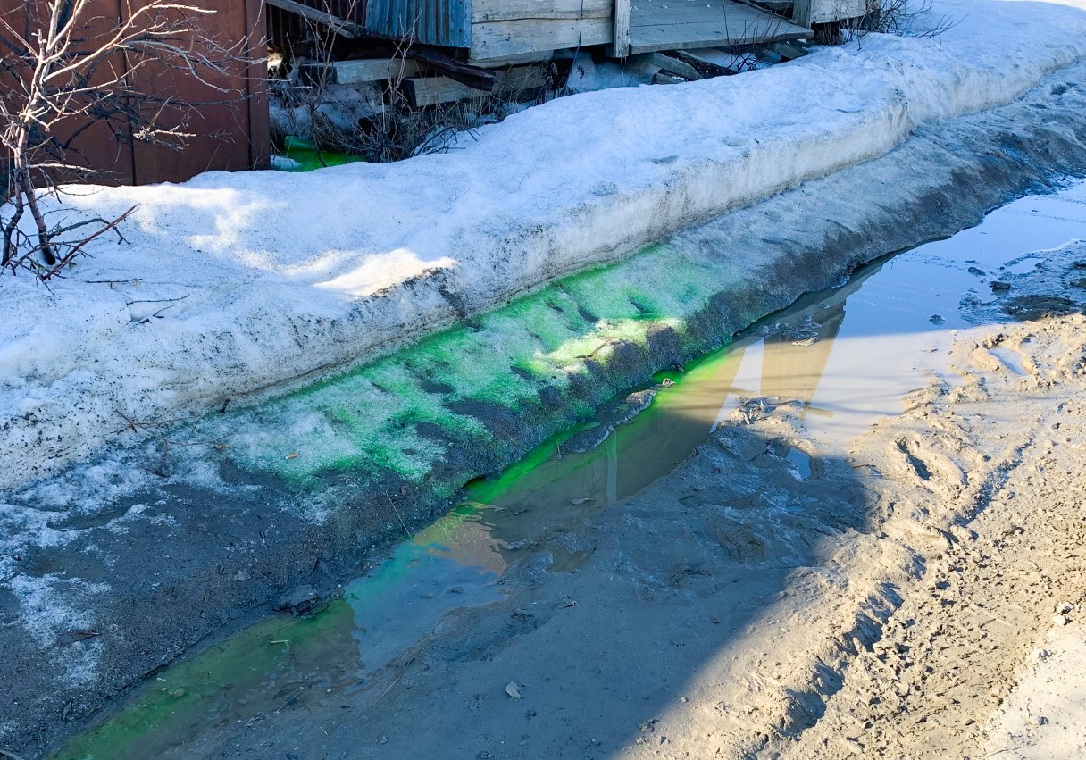 A photo of a snow bank with green liquid on it seeping into the street below in Nome, Alaska.