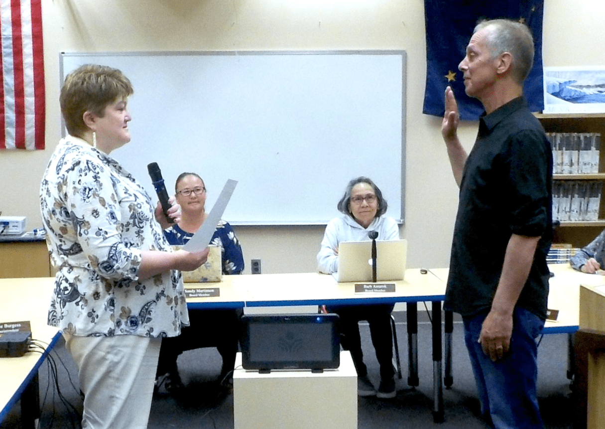 Bob Metcalf is sworn in by Jamie Burgess. Photo by Nome Board of Education, used with permission.
