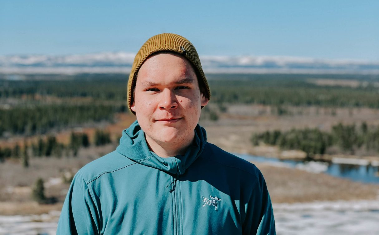 Young man looking into camera with a yellow beanie and blue jacket. Mountains and trees in the background.