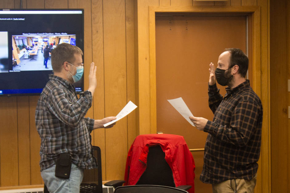 Two masked men facing each other. Both are holding a piece of paper in one hand and then have the other hand raised. They are inside of a building.