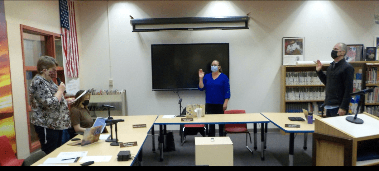 In a room 3 masked people stand facing a woman holding her right hand up.
