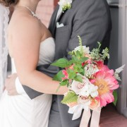 Bride and groom with coral charm peony bouquet