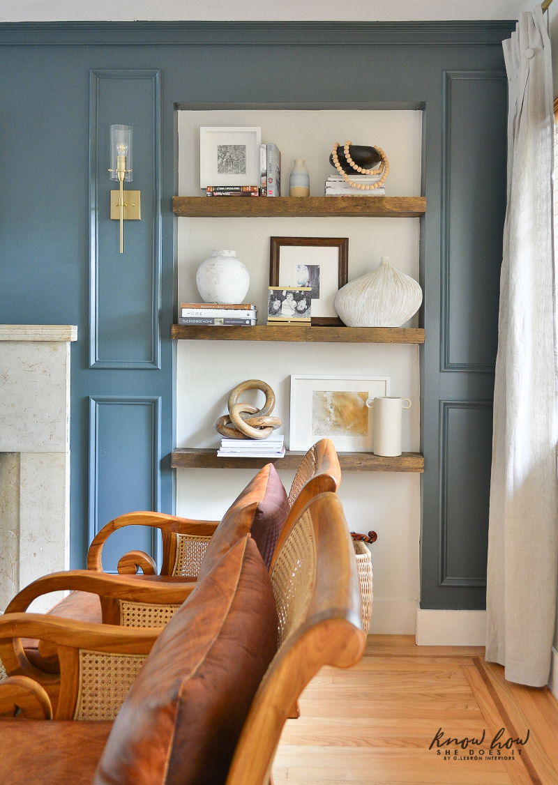 White vases and some pop of blue items were added to this wall shelves.