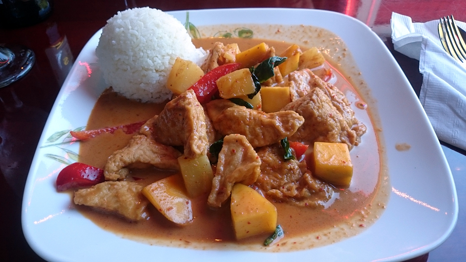 A delicious-looking Thai red curry on a funky square white plate.