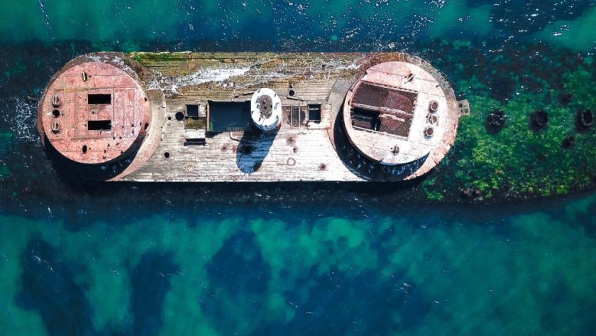 Bird's eye view of a sunken battleship in clear blue water.