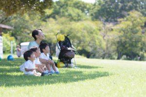 木陰の芝生の上に座る家族