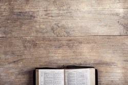 photo of wooden table with partially shown open bible at bottom of page