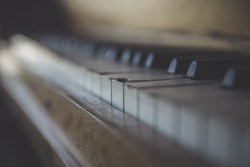 Out of focus picture of old piano keyboard with chipped keys.