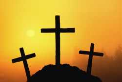 Three silhouetted crosses on a mountain top with the sun shining at sunrise with yellow and orange colors