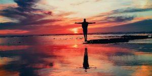 eine Frau steht am Strand im Wasser während eines Sonnenuntergangs
