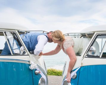 Creative shot of Bride & Groom on Wedding Day kissing through the windows of VW Kombi Vans