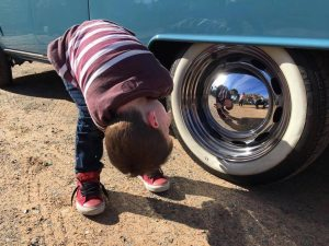 Cute photo of boy staring into hub cap of 1960s Vintage Volkswagen Kombi Van at Wedding