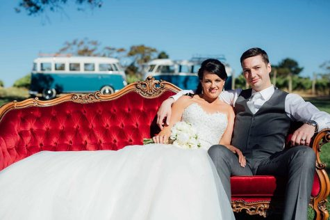 Bride & Groom sitting on Red Velvet Couch in front of 2 Hire Cars, Vintage Blue 1960s Volkswagen Kombi Vans on their Wedding Day