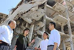 爆撃されたビルの前で、清田明宏UNRWA保健局長らの話を聞く谷合、岡本の両氏=9月30日 パレスチナ自治区ガザ地区