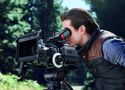 A man looking into the viewfinder of the Blackmagic URSA Mini cinema camera.
