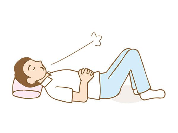 寝て腹式呼吸をしている男性