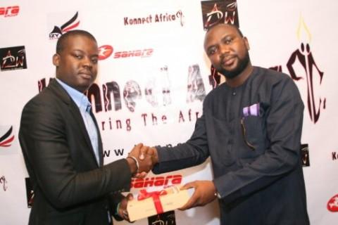 Mudiaga receives the first-prize [on behalf of Dr. Tombari] from Babatomiwa Adesida of Sahara Foundation