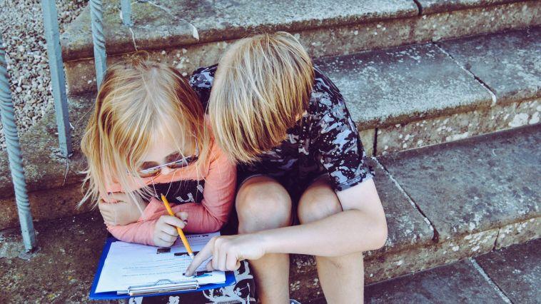 iki çocuk ders çalışıyor sokakta