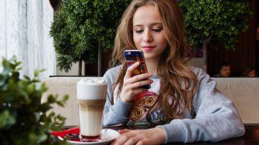 cafede telefonuna bakan genç kız