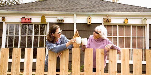 çitlerin arkasında iki kadın komşu gülüyor
