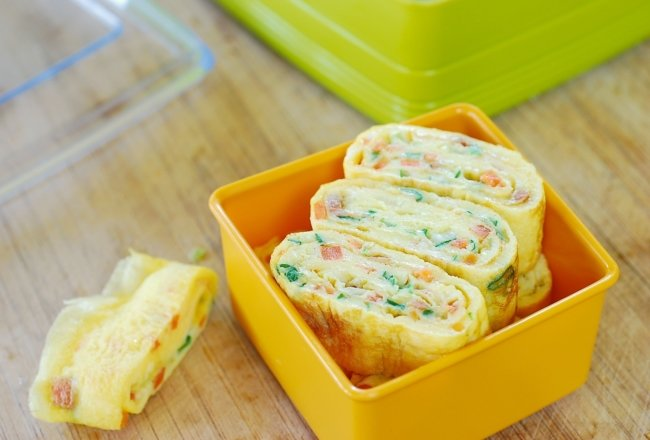 Korean rolled omelette with chopped carrot and scallion in a tupperware
