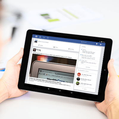 Person holding a tablet with Facebook feed