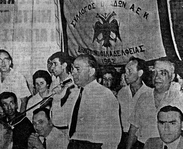 Ο Νίκος Γκούμας μιλάει στους φίλους της ΑΕΚ στη Νέα Φιλαδέλφεια, μετά την κατάκτηση του πρωταθλήματος 1962-63. Στη δεξιά πλευρά της φωτογραφίας ο Δήμαρχος Νέας Φιλαδέλφειας Νίκος Τρυπιάς. Πηγή: Αθλητική Ηχώ, 26/6/1963