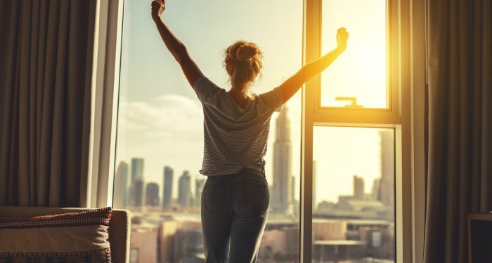 happy woman stretches and opens the curtains at window in morning