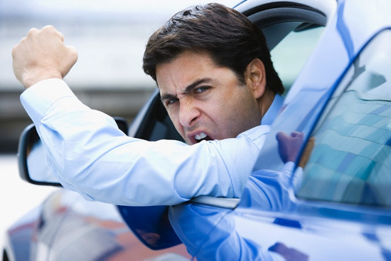 Road rage businessman shaking his fist --- Image by © Steve Hix/Somos Images/Corbis