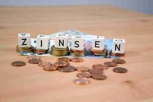 Würfel mit Aufschrift Zinsen Münzen und Geldscheine im Hintergrund