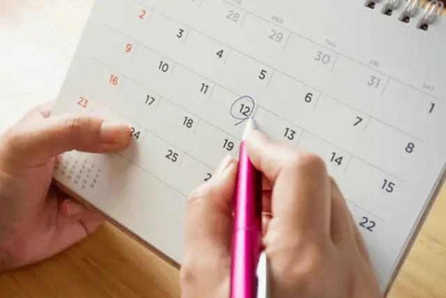 female hand circling date on calendar