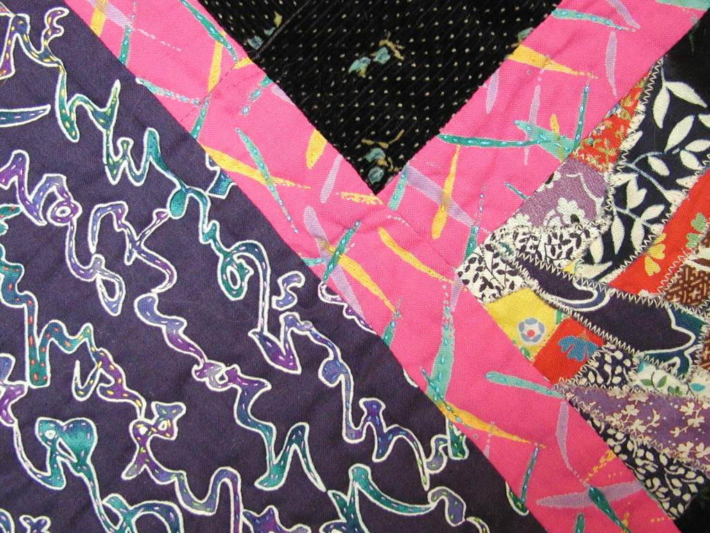 Tiny quilting stitches follow fabric motifs.