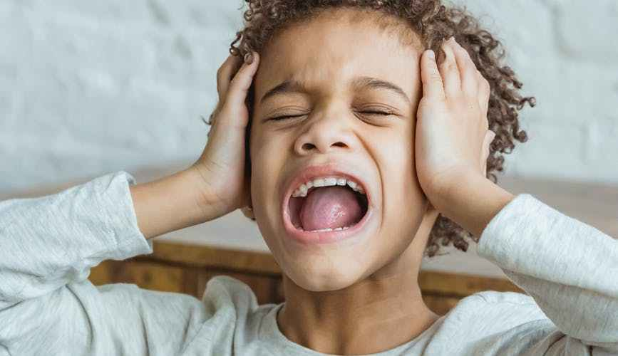 unhappy black boy with closed eyes screaming in room