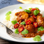 Portrait image of a chicken pathia or patia curry served on a plate with rice, chilli slices and fresh coriander with text overlay