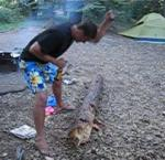 karl chopping wood while holding a beer bottle
