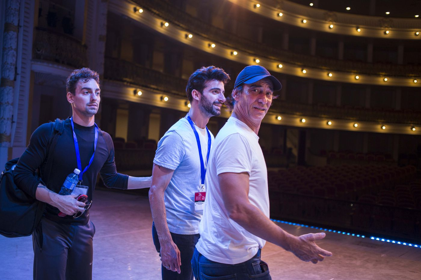 In this Oct. 30, 2018 photo, Cuban expatriate ballet dancers Daniel Sarabia, left, Rolando Sarabia, center, and their father, retired dancer, Rolando Sarabia, visit the grand theatre in Havana, Cuba. As a young dancer compared with ballet legends Vaslav Nijinsky and Mikhail Baryshnikov, Rolando Sarabia made headlines around the world when he abandoned Cuba in 2005 for a career in the United States. (AP Photo/Desmond Boylan)