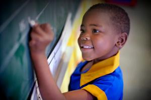Kagiso Shanduka Trust (KST), South African school child writing on chalkboard in class